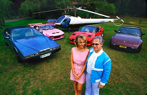 Dr Geoffrey and Leanne Edelsten posing with their transport fleet