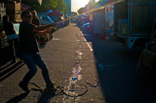 A market worker hauling a stall cover into place as the sun begins to slant down Salamanca Place © Rob Walls 2012