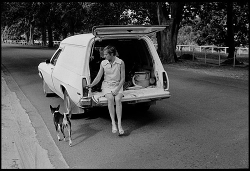 An off-duty cleaner walks her dog from the back of a station wagon, in Centennial Park, Sydney © Rob Walls 1977